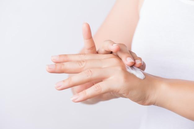 Hände der jungen frau, die befeuchtende handcreme auftragen.