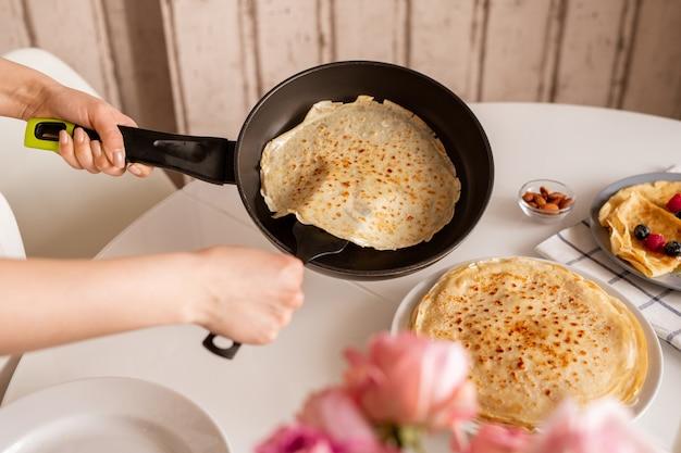 Hände der jungen frau, die bratpfanne über küchentisch hält, während heißer appetitlicher pfannkuchen nimmt, um ihn auf andere crepes auf teller zu setzen