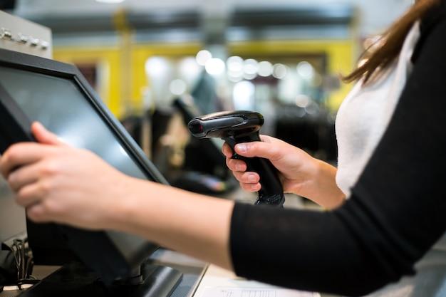 Hände der jungen frau, die rabatt / verkauf auf einer quittung, touchscreen-registrierkasse, markt / geschäft scannen / eingeben