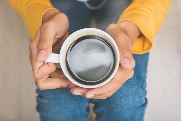 Hände der jungen frau, die schale heißen schwarzen kaffee halten
