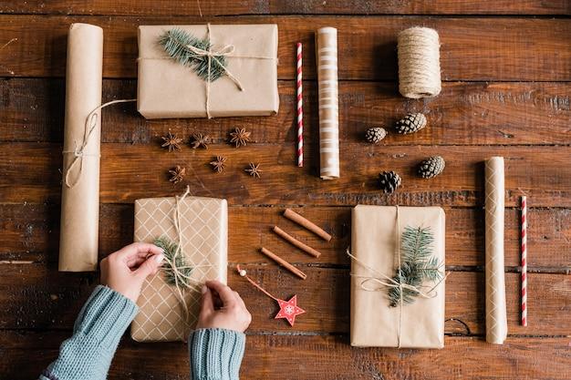 Hände der jungen frau im blauen pullover, der knoten auf einer der geschenkboxen macht, während sie fertig sind, um geschenke zu packen