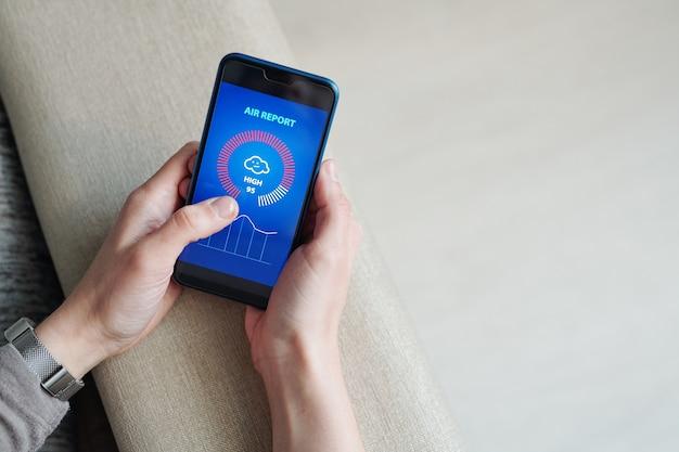 Hände der jungen frau mit dem smartphone, das durch luftbericht mit grafik und diagramm auf touchscreen schaut
