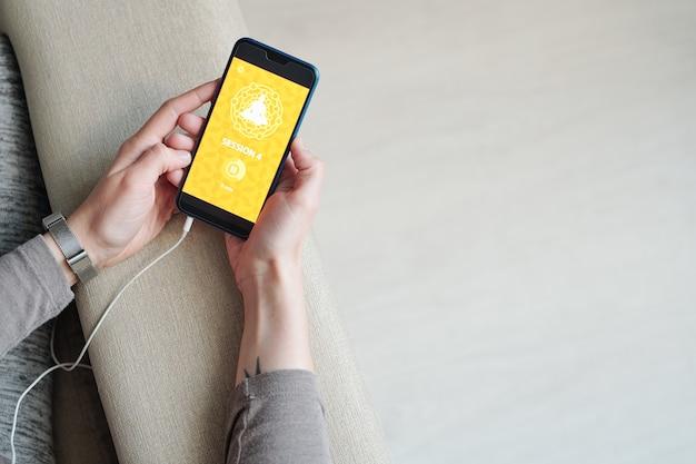 Hände der jungen frau mit smartphone warten auf download der videositzung des yoga-kurses