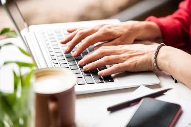 Hände der jungen geschäftsfrau auf laptop-tastatur, die im netz surft, daten eingibt oder e-mails abruft