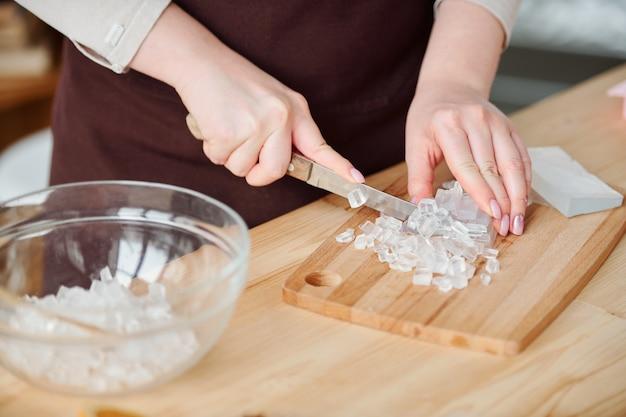 Hände der jungen handwerkerin mit messer, das transparente seifenmasse an bord durch holztisch schneidet