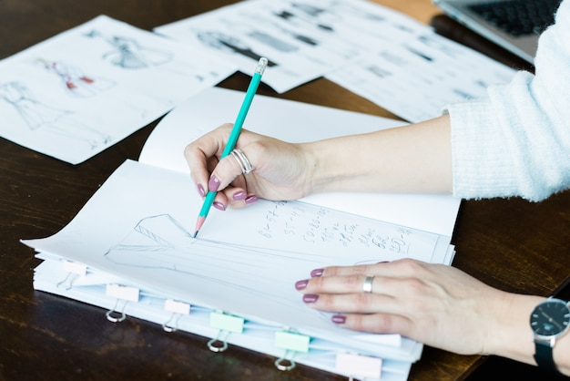 Hände der jungen weiblichen zeichnungsmodeskizze auf der leeren seite des notizblocks für neue saisonale sammlung beim sitzen am tisch