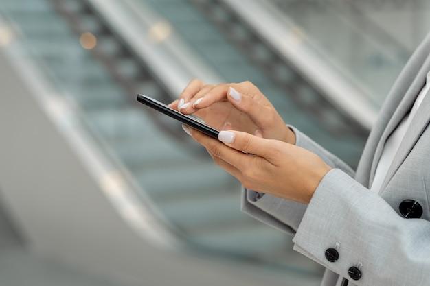 Hände der jungen zeitgenössischen geschäftsfrau, die im smartphone scrollt