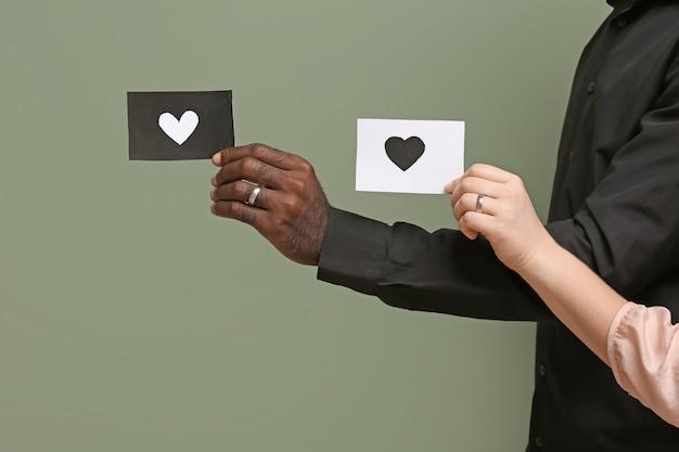 Hände der kaukasischen frau und des afroamerikanischen mannes, die papierblätter mit gezeichnetem herzen auf farboberfläche halten. rassismus-konzept