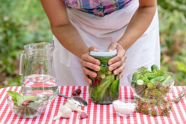 Hände der köchin schließen die dose mit gurken zur konservierung