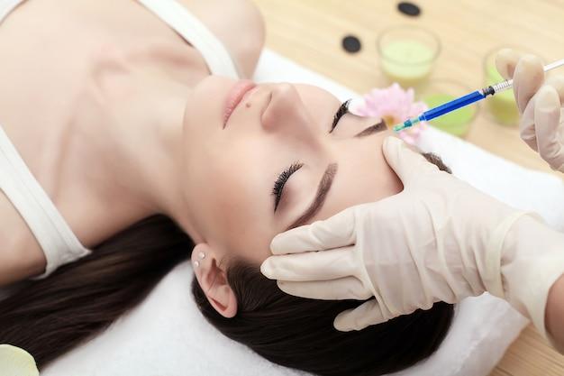 Hände der kosmetikerin, die injektion in gesicht, lippen macht. junge frau bekommt schönheits-gesichtsinjektionen im salon. gesichtsalterung, verjüngung und flüssigkeitszufuhr. ästhetische kosmetologie. nahansicht.