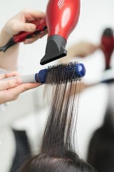 Hände der kosmetikerin, die langes brünettes haar des kunden mit rotem haartrockner und haarbürste im professionellen schönheitssalon trocknet.