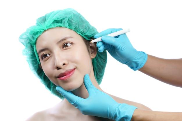 Hände der kosmetikerin, die linien auf asiatischem frauengesicht für plastische chirurgie zeichnet.