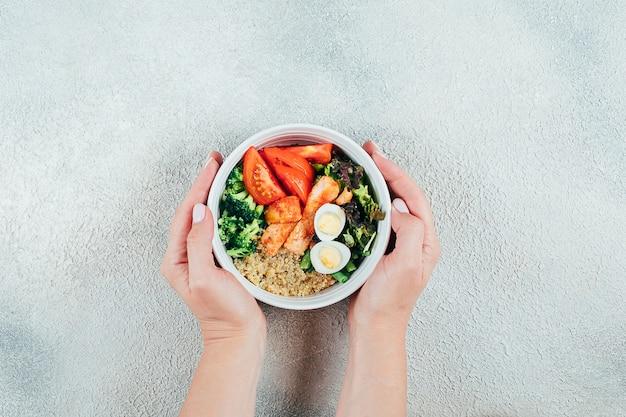 Hände der mädchen, die lachssackschüssel halten. fischsalat mit lachs, couscous, salatmischung, gemüse