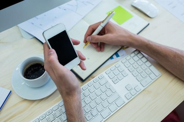 Hände der männlichen grafikdesigner auf ein tagebuch zu schreiben und halten handy