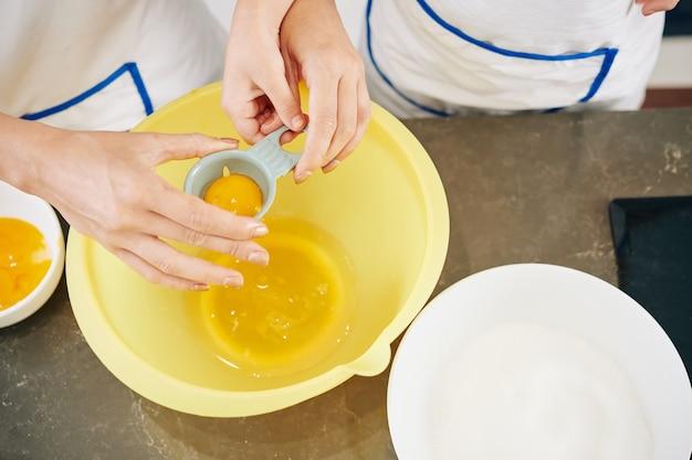 Hände der mutter zeigen tochter, wie man plastikwerkzeug benutzt, wenn eigelb von eiweiß getrennt wird