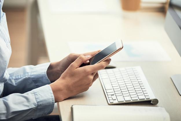 Hände der unerkennbaren frau, die smartphone am schreibtisch im büro verwendet