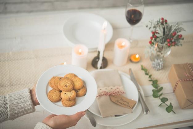 Hände der unerkennbaren frau platte von keksen auf reizende weihnachtstabelle setzend