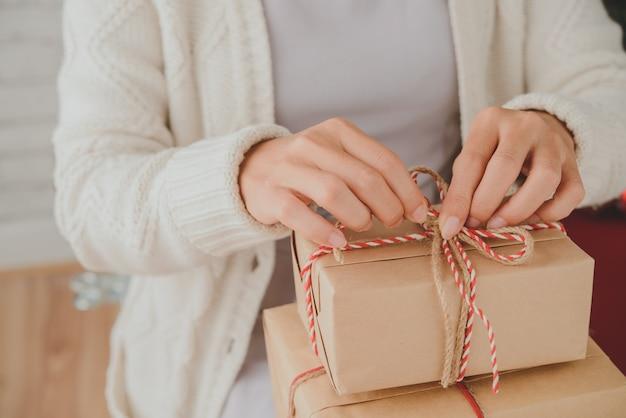 Hände der unerkennbaren frau weihnachtsgeschenke mit dekorativer schnur oben bindend