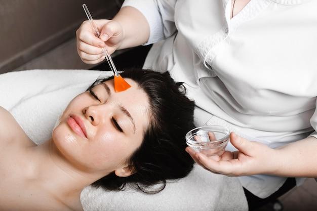 Hände der weiblichen kosmetikerin, die eine transparente maske mit einem pinsel auf ein weibliches gesicht anwenden.