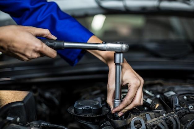Hände der weiblichen mechaniker wartung eines autos