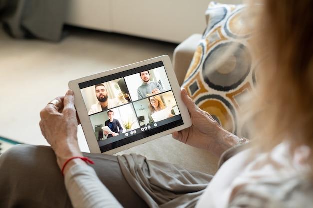 Hände der zeitgenössischen frau mit digitalem tablett, das online mit vier freunden oder verwandten kommuniziert, während sie für quarantäne zu hause bleiben