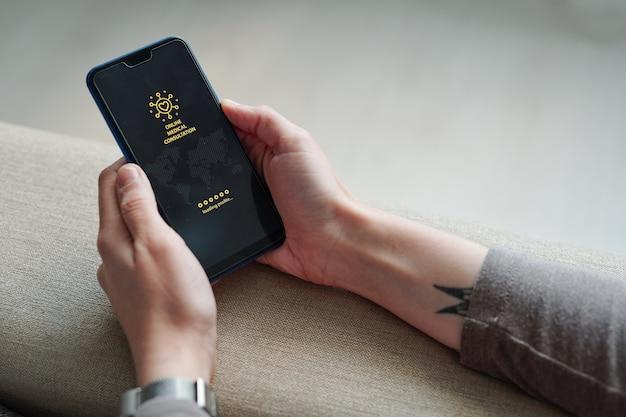 Hände der zeitgenössischen jungen frau, die smartphone mit homepage der medizinischen website auf dem bildschirm hält