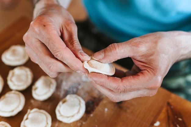 Hände des älteren mannes, der kleine hausgemachte ungekochte knödel mit fleisch auf küchentisch kocht und formt