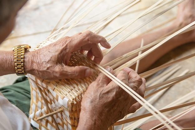 Hände des älteren mannes, die manuell bambus spinnen.