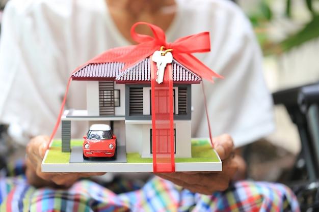 Hände des älteren mannes, die musterhaus mit rotem band und das auto mit schlüsseln halten