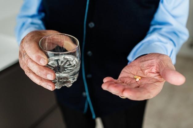 Hände des älteren mannes im blauen hemd, das ein glas wasser und medikamente hält