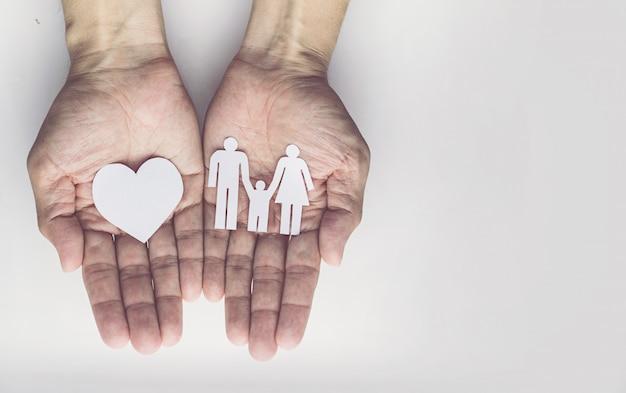 Hände des alten mannes, die kleine vorbildliche familie halten