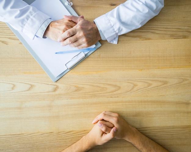 Hände des anonymen doktors und des patienten auf tabelle
