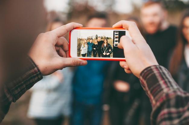 Hände des anonymen mannes, der smartphone verwendet, um foto der gruppe junger freunde in der natur zu machen. ernten sie hände, die foto von freunden machen