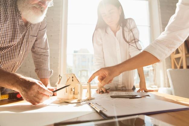 Hände des architekten-ingenieurs und des jungen paares während der präsentation des zukünftigen hauses seitenansichttisch mit dokumenten, blaupause. erstes zuhause, industrie, gebäudekonzept. umzug in einen neuen live-ort.