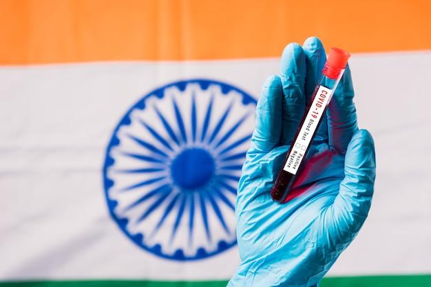 Hände des arztes, der handschuhe trägt, die das blutreagenzglas-coronavirus (covid-19) -virus im labor auf der flagge indien halten