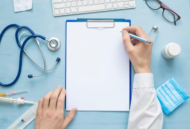 Hände des arztes, die ein rezept oder einen medizinischen bericht auf ein leeres blatt papier schreiben.