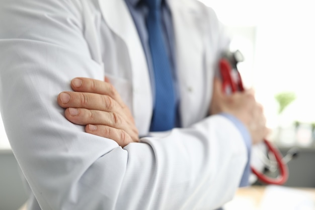 Hände des arztes im weißen kittel, der stethoskop hält
