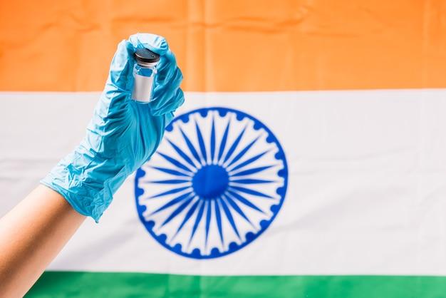 Hände des arztes tragen handschuhe, die coronavirus (covid-19) fläschchenimpfstoff und spritze auf flagge indien halten