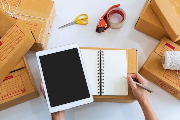 Hände des asiatischen geschäftsinhabers, der tablette beim schreiben auf notizbuch mit pappkartons hält
