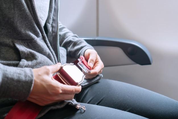 Hände des asiatischen weiblichen passagiers, der sicherheitsgurt festhält, während auf dem flugzeug sitzen. reisekonzept.