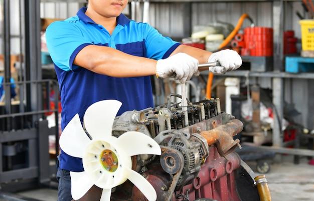 Hände des automechanikers im autoreparaturdienst in der autowerkstatt