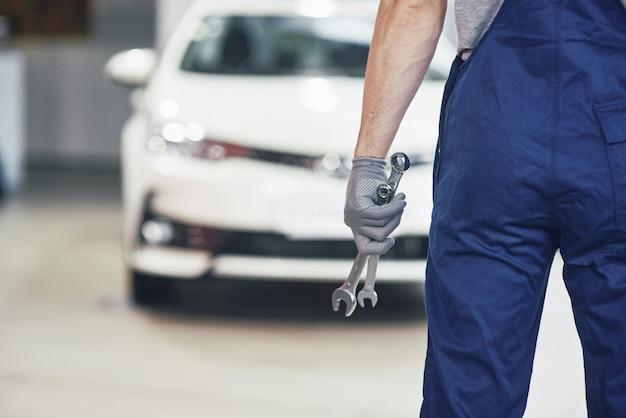 Hände des automechanikers mit schraubenschlüssel in der garage
