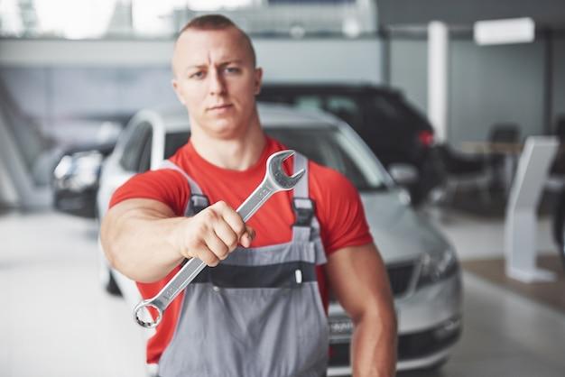 Hände des automechanikers mit schraubenschlüssel in der garage.