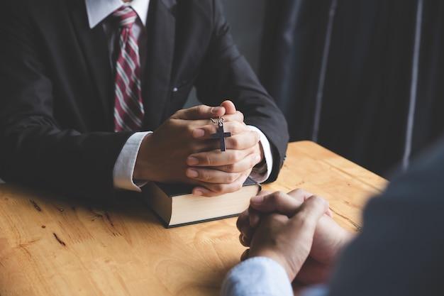 Hände des betens des jungen mannes und der bibel auf einem hölzernen schreibtisch
