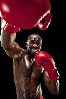 Hände des boxers auf schwarzem hintergrund. kraft-, angriffs- und bewegungskonzept. fit afroamerikanisches modell in bewegung. afro muskulöser athlet in sportuniform. sportlicher mann beim boxen