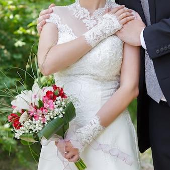 Hände des bräutigams und der braut mit eheringen