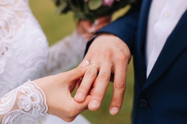 Hände des bräutigams und der braut mit ringen