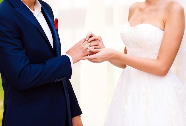 Hände des bräutigams und der braut trägt einen ring am finger am tag