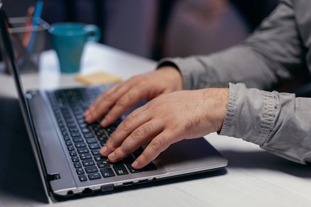Hände des büroleiters über tastatur am unternehmensarbeitsplatz. nahaufnahme von männlichen händen, die auf laptop-tastatur im büro tippen. geschäft, von zu hause aus arbeiten, online-konzept studieren
