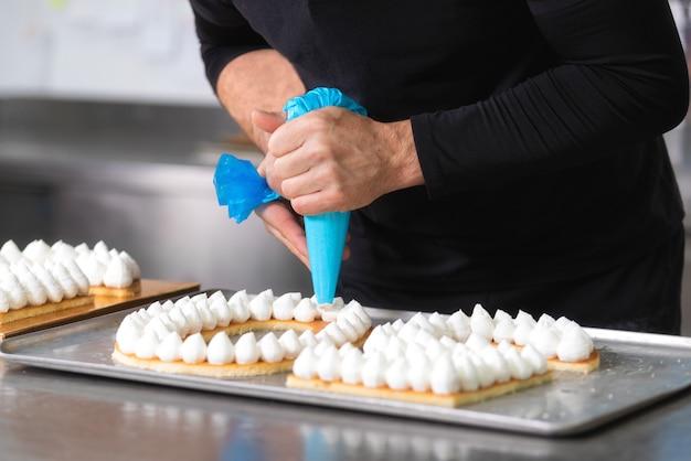 Hände des chefs mit süßigkeitenbeutelcreme, die einen fünfzig jahre alten geburtstagskuchen vorbereitet